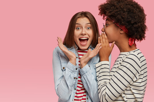 Emotional European woman clasps hands and exclaims loudly as hears rumors from best friend. Afro American woman whispers secret at companions ear, stands sideways, gossip together, stand indoor