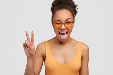 Joyful black woman with peace hand sign, blinks eye and shows tongue, has curly Afro hair combed in bun, dressed casually, poses against white background, has fun with friend, isolated on white Wall mural