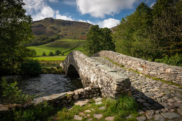 Old Cobbled Stone Bridge over River Derwent in the Borrowdale Valley, Lake District, England, UK
