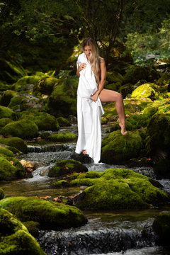 Woman posing naked in the river stream