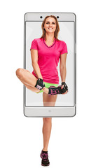 Portrait of smiling athletic woman stretching her leg, concept virtual reality of the smartphone. going out of the device
