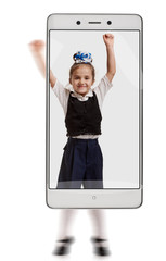 Photo of happy smiling schoolgirl jumping on white background. conceptual image with a smartphone, demonstration of device capabilities