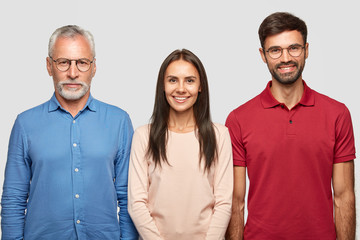 Three people in shot. Serious senior male pensioner dressed in formal shirt, stands near his daughter and son, pose together against white backgrounf for making family portrait. Relationships concept
