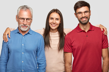 Friendly grandfather, granddaughter and grandson stand closely and embrace, make family photography, have positive exressions, rejoice meeting after long time, isolated over white background.
