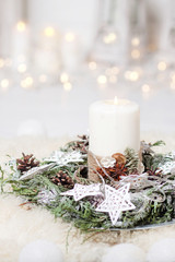 Christmas candles and snowy fir branches over white wooden background with lights.  New Year's decoration with a fir tree in white tones.