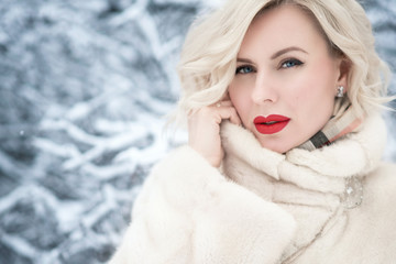 Close up portrait of beautiful blond blue-eyed lady with perfect make up holding a collar of her luxurious fur coat.