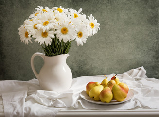 still life with bouquet of daisy flowers in a jar and fresh pears