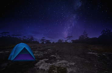 Illuminated Blue Camping Tents of Travel Camper in Starry Night with Milky Way on the Peaceful Rock Mountain - Outdoor Activity in Summer