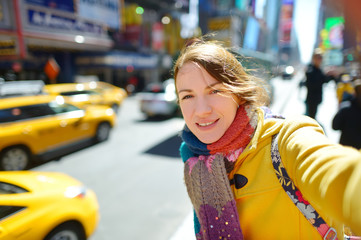 Happy young woman tourist sightseeing at Times Square in New York City. Female traveler enjoying view of downtown Manhattan.