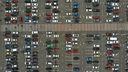 Aerial. Parking lots with a lot of cars and pedestrian crosswalk between them. Bird eye view above.