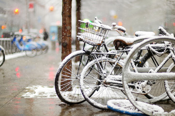 Row of old bicycles covered with snow after massive snowfall in New York City at wintertime.