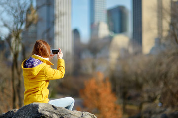 Happy young woman tourist taking pictures at Central Park in New York City. Female traveler enjoying views of downtown Manhattan.