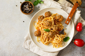 Italian style pasta dinner. Spaghetti with Meatballs with Tomato Sauce on stone or concrete table. Top view flat lay background. Copy space.