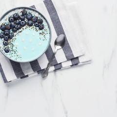 Top view of blue yogurt smoothie bowl made with blueberry, coconut flour, chia seeds and sugar pearls on white marble table with copy space. Square crop.