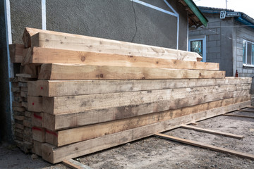 Pine wood timber stack of natural rough wooden boards on building site. Industrial timber building materials for carpentry, building, repairing and furniture, lumber material for roofing construction.