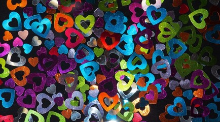Colorful shiny hearts on a black background.