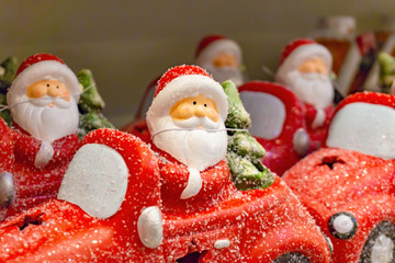Santa Claus on a red car, a set of festive toys in the store.
