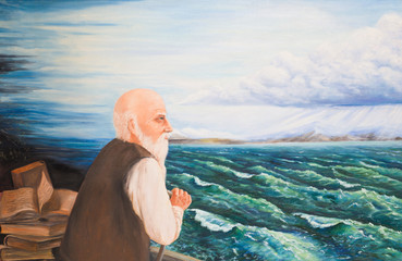 A gray-haired bearded old man stands by the lake and looks into the distance