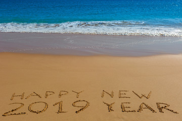 HAPPY NEW 2019 YEAR inscription written in the wet yellow beach sand