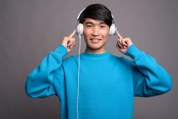 Young Asian man listening to music against gray background