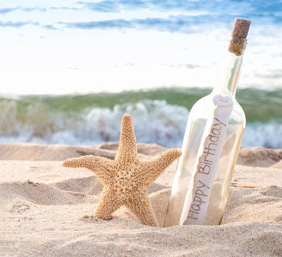 close up of starfish and happy birthday message in a bottle on the seashore with water background