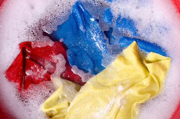Washing color clothes in basin enemale powdered detergent, top view