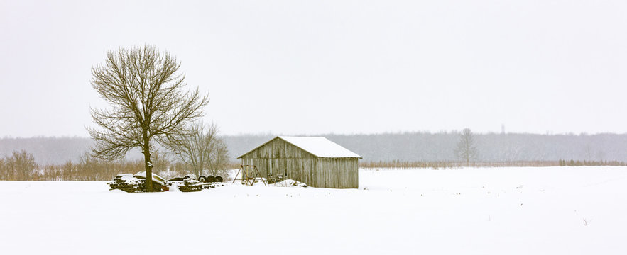 Antique barn in a snowy winter scene in rural Quebec, Canada.