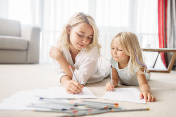 Mother and daughter draw lying on the floor