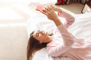 Young woman lies in bed and using phone
