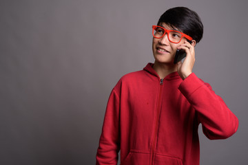 Young Asian man wearing red jacket with eyeglasses against gray