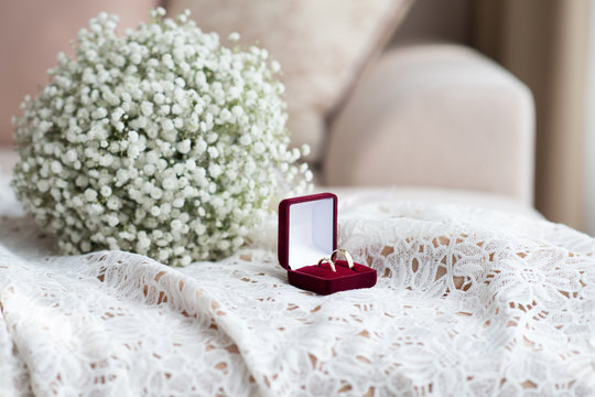 Wedding rings in a red velvet box and a bridal bouquet over a white lace wedding dress