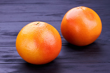 Close up two grapefruits on dark wood. Tasty exotic fruits on black wooden background.