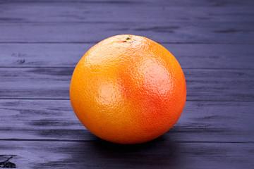 Whole fresh grapefruit on dark wood. Fresh juicy fruit close up. Healthy food concept.