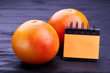 Two fresh grapefruits and blank paper sheets. Whole organic grapefruits and small paper notepad on wooden background. Diet and healthy eating.
