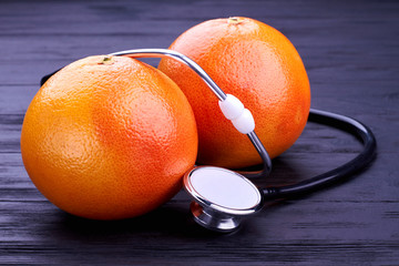Two fresh grapefruits and stethoscope. Whole organic grapefruits and medical tool on wooden background. Concept of healthcare.