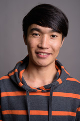 Young Asian man wearing striped hoodie against gray background
