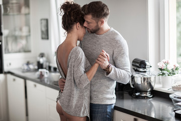 Intimate couple dancing in the kitchen. Wall mural