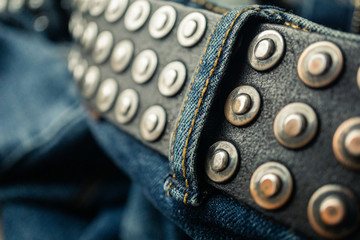close up detail of an unbuckled leather belt on a faded pair of blue jeans