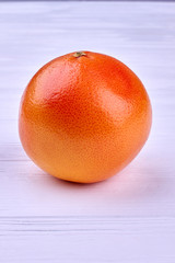Whole juicy grapefruit on light background. Tasty citrus fruit on wooden background with copy space, vertical image.