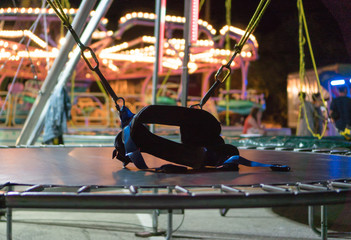 Bungee trampoline in amusement park at night.