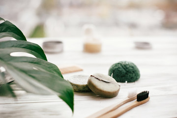 Eco friendly natural bamboo toothbrushes, shampoo bar, toothpaste in glass, wooden brush and...