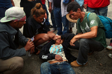 Milton, a migrant man, part of a caravan of thousands traveling from Central America en route to the United States, lays injured on the floor after falling from a truck whilst hitchhiking along the highway to Isla from Sayula de Aleman