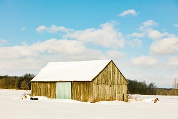Antique barn in rural Quebec Canada in a snowy seasonal background.