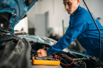 Car repairman with multimeter, battery inspection