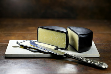 mature cheddar cheese with silver knife and ceramic cutting board isolated on rustic wooden background