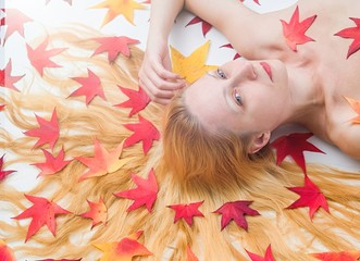 Portrait of the woman with colorful autumn leafs in the hair