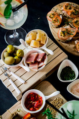 appetizers for aperitif with canapes, olives, cheese, ham, sandwiches and toast