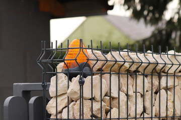 Orange room alarm light located on a brick fence post. Intercom apartment building at the entrance to a private protected area. Hazard alert. Intercom for door curtain. Property Protection and Securit