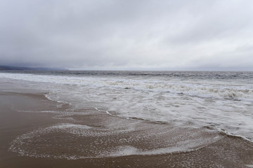 Small waves roll into empty beach on overcast day