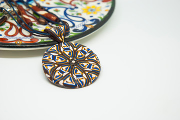 Mandala ethnic pendant isolated in woman hand. Handmade jewelry of polymer clay. Winter necklace.